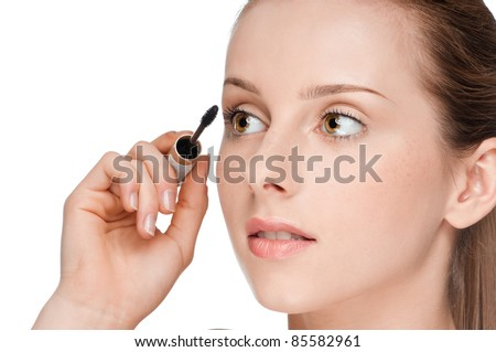 Beautiful woman applying mascara on her eyelashes - isolated on white