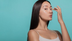 Beautiful woman applying moisturizer to her nose against blue background.. Woman applying beauty cream on her face.