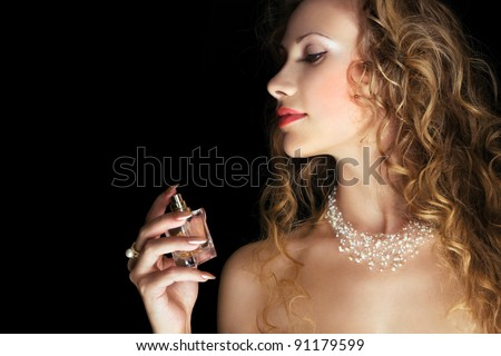 Beautiful woman applying perfume on her neck. Space for text.