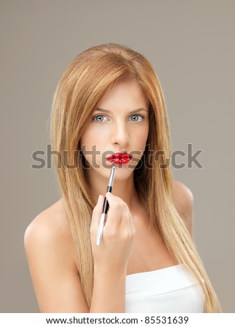 beautiful woman applying red lipstick with brush