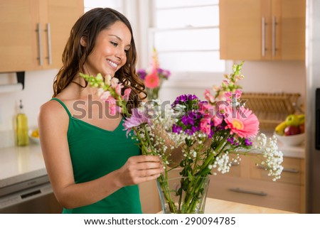 Beautiful woman arranging flowers picked from her garden at home happy and joyful