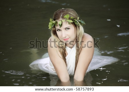 Beautiful woman as a forest nymph on the river