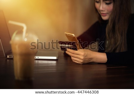 Beautiful woman asian girl using smartphone to find a product shopping online and holding a credit card to pay online shopping cart easy and quickly in holiday deal with low prices promotion concept.
