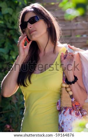 Beautiful woman at a shopping center, calling