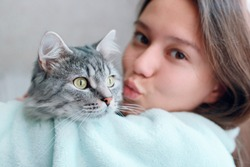 Beautiful woman at home kissing and hug her lovely fluffy cat. Gray tabby cute kitten with green eyes. Friend of human. Good sunny morning.