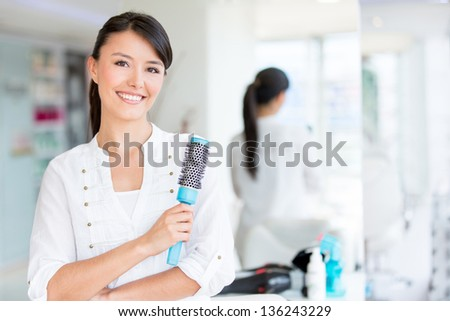 Beautiful woman at the beauty salon holding a hair brush