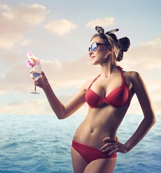 Beautiful woman at the seaside holding a drink