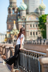 Beautiful woman at the summer waterfront in Saint Petersburg. Girl outdoors with The Church of the Savior on Spilled Blood background