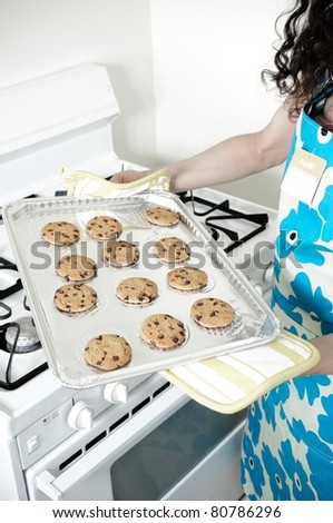 Beautiful woman baking cakes and cookies in a white home kitchen oven