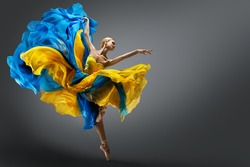 Beautiful Woman Ballet Dancer Jumping in Air in Colorful Fluttering Dress. Graceful Ballerina Dancing in Yellow Blue Gown over Gray Studio Background