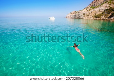 Beautiful woman bathing in clear sea. Active vacation on the beach. #207328066