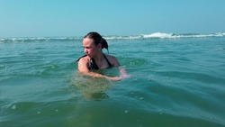 Beautiful woman bathing in the sea or ocean. Tourist woman swimming in ocean at summer resort on tropical. The girl is bathing in the sea and it is covered by a wave