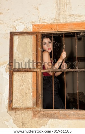 Beautiful woman behind rusty bars in a derelict old house