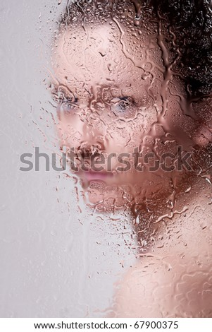 Beautiful woman behind the glass with water drops looking directly at camera