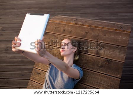 Beautiful woman blogger making photo on touch pad while relaxing outdoors on a wooden bench in sunny summer evening. Pretty female having online video call via digital tablet during leisure time