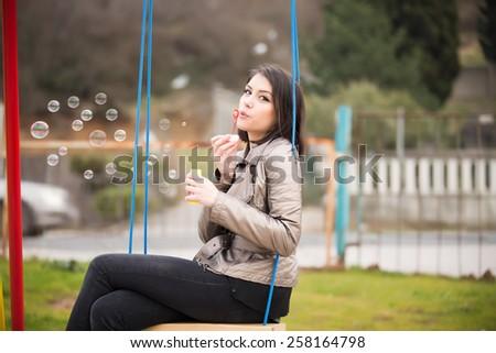 Beautiful woman blowing bubbles on the playground.Young woman blowing bubbles swinging in the park.Gorgeous flirty brunette woman starts soap bubbles in park