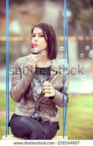 Beautiful woman blowing bubbles toned with a retro vintage instagram filter.Young woman blowing bubbles swinging in the park.Gorgeous flirty brunette woman starts soap bubbles in park