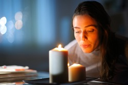 Beautiful woman blowing out candles in the living room at home in the night