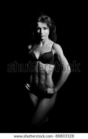 beautiful woman bodybuilder posing in black bikini on black background