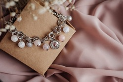 Beautiful woman bracelet with white and pink beads on the craft box. Image with selective focus and toning.