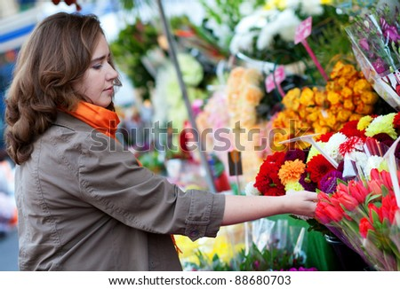 Beautiful woman buying flowers at market - stock photo