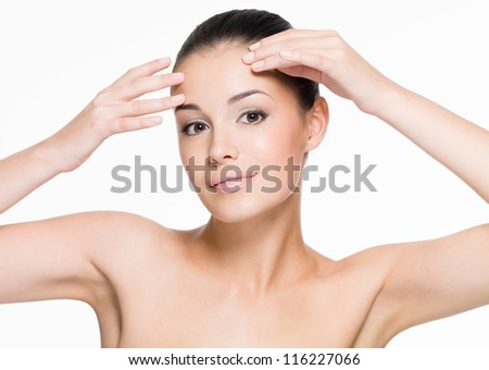 Beautiful woman cares of forehead - posing at studio  isolated on white