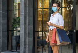 beautiful woman carries a shopping bag and wears a mask to prevent Covit 19. Walking out of the shopping mall