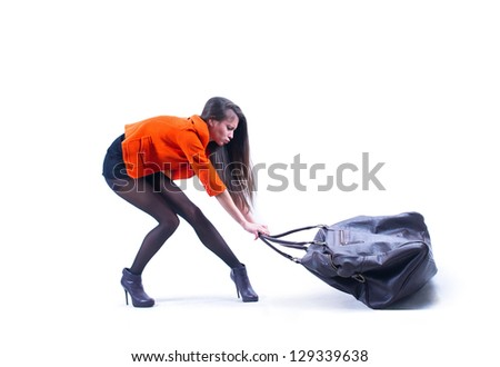 Beautiful woman carrying heavy bag  with some difficulty