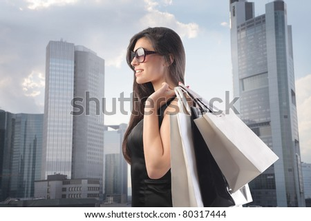Beautiful woman carrying some shopping bags with cityscape in the background