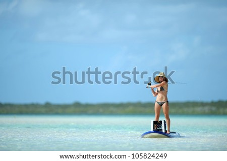 Beautiful woman casting fishing rod while paddleboarding in the Caribbean - stock photo