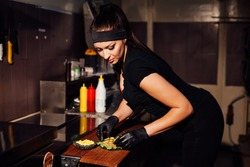 beautiful woman chef prepares a hamburger in the kitchen of the restaurant