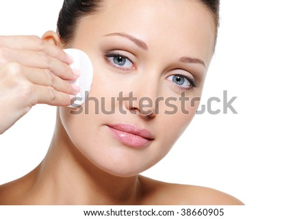 Beautiful woman cleaning her pretty face with cotton swab