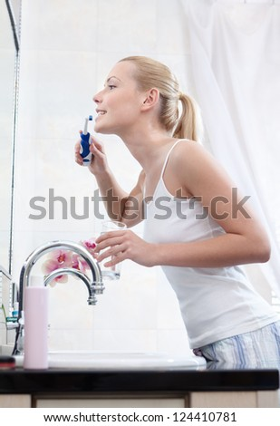 Beautiful woman cleans her teeth in bathroom