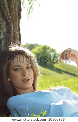 beautiful woman close up laying under the tree outdoor with field on the background with room for text. Soft summer colors