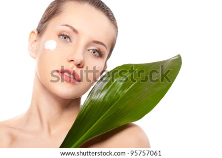 beautiful woman closeup face portrait with green leaf and cream on face