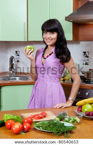 Beautiful woman cooking healthy food in the kitchen - indoors