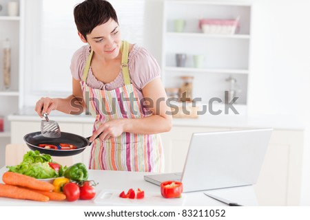 Beautiful woman cooking with receipt on laptop in the kitchen