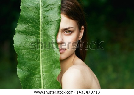 beautiful woman covered her face with a green leaf #1435470713