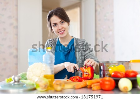 beautiful woman cuts red pepper at her kitchen at home
