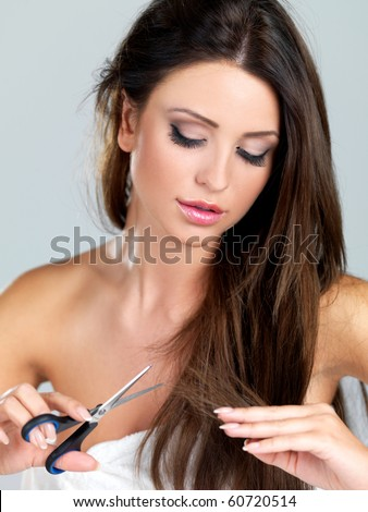 Beautiful woman cutting her hair tips with scissors