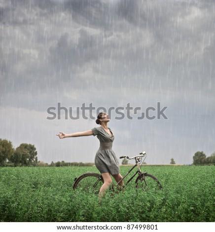 Beautiful woman cycling on a green meadow in the rain