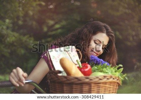 Beautiful woman cyclist with a basket. Bicycle Basket. To buy food. Food, a bouquet of flowers. Beautiful girl with retro bicycle. Products on a bicycle. Gastronomy. Healthy food.