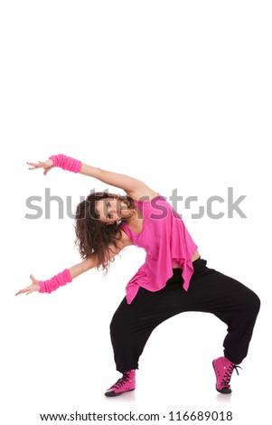 beautiful woman dancer bending to her side with arms streched, while looking into the camera