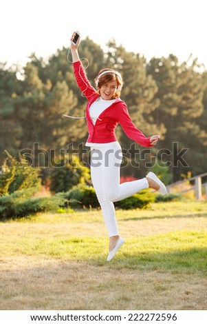 Beautiful woman dancing and jumping. Woman with headphones listening to music on her head. Attractive young woman jumping in the air against nature background.