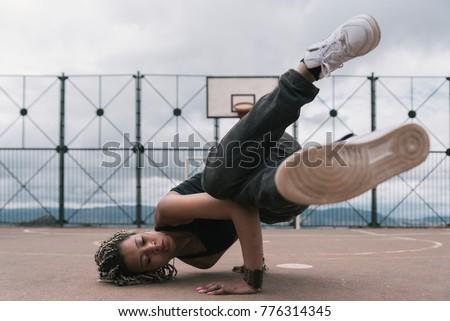Beautiful woman dancing hip hop in basketball court. Hip hop Concept.