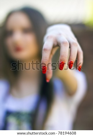 Beautiful woman demonstrates long red nails