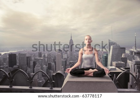 Beautiful woman doing a yoga exercise on he rooftop of a skyscraper