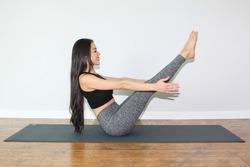 Beautiful woman doing a yoga pose called boat pose or navasana.