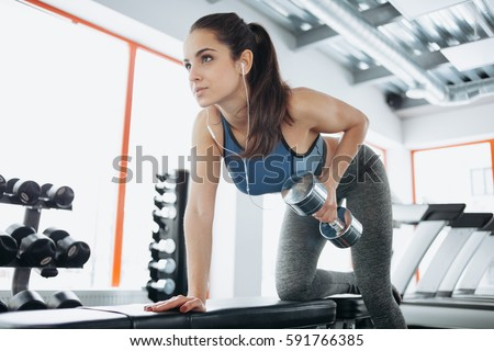 Stock Photo Beautiful woman doing exercises with dumbbell in gym. Young concentrated girl looking near and working out. She has headphones in her ears so she is enjoying music also