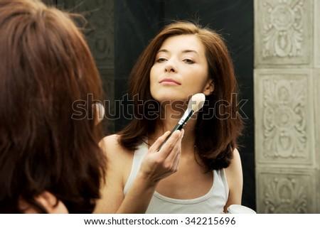 Beautiful woman doing make up in bathroom. #342215696